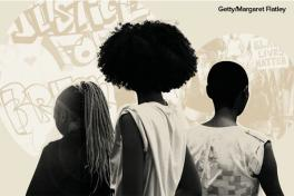 Black women and girls in front of protest art and march (image by Margaret Flatley at Getty)
